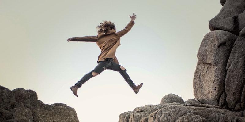 Woman jumping from one cliff top to another