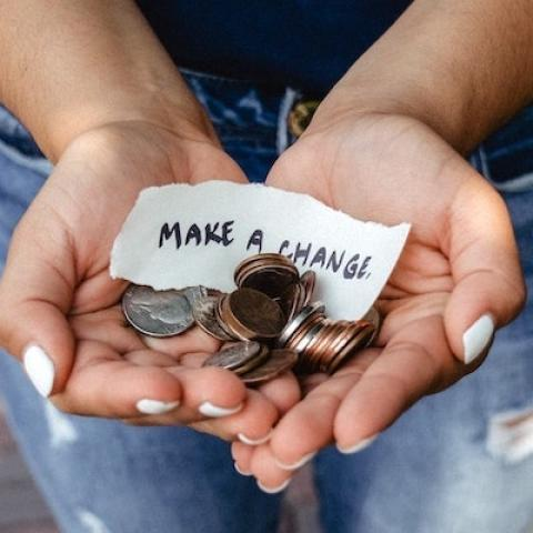 "Woman's hands holding coins and a slip of paper that says ""Make a Change"""
