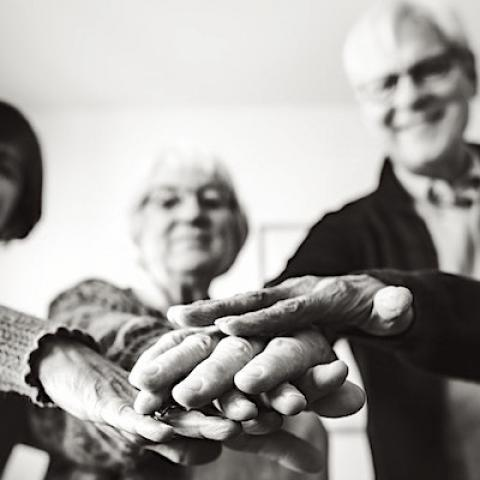 Group of older adults in a circle with hands in